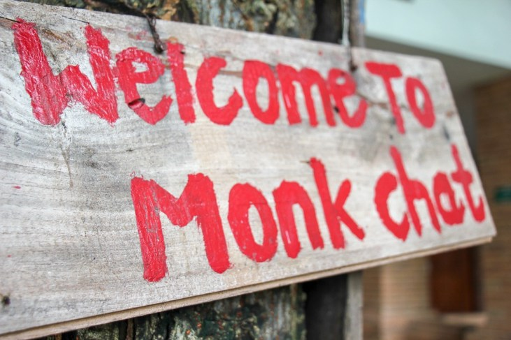 Welcome to Monk Chat wooden sign hanging in Chiang Mai, Thailand