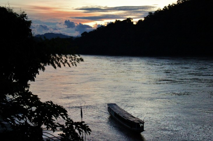 River boat heads upstream at sunset on Mekong River in Luang Prabang, Laos