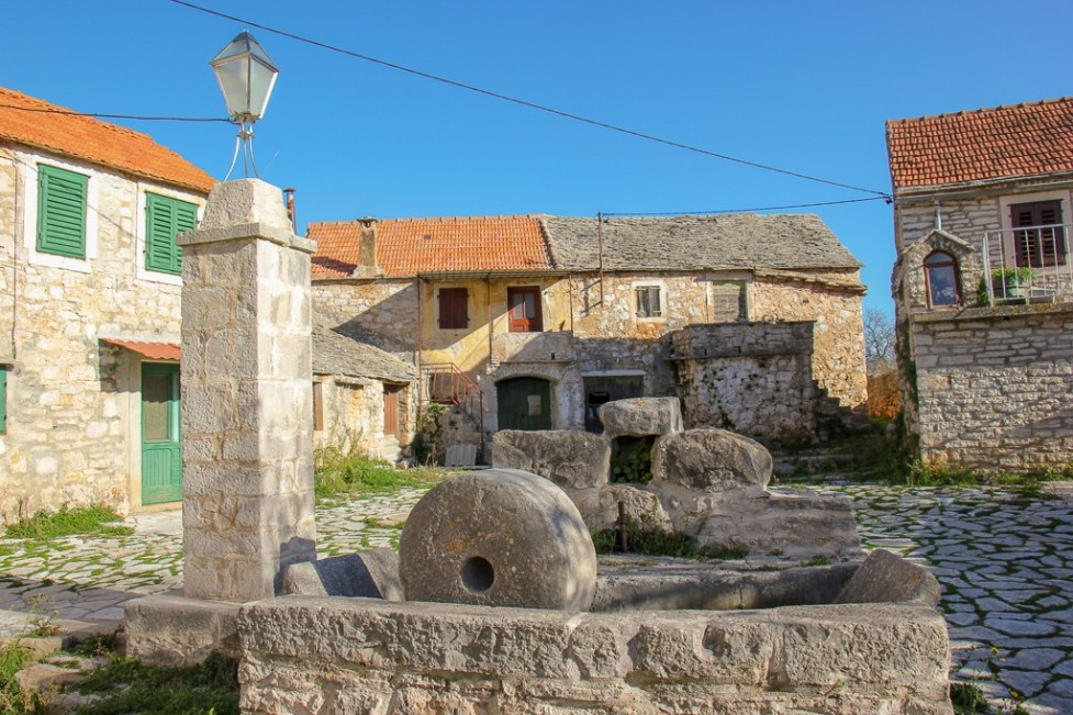 Historic artifacts on main square in Mala Rudina in Stari Grad on Hvar Island, Croatia
