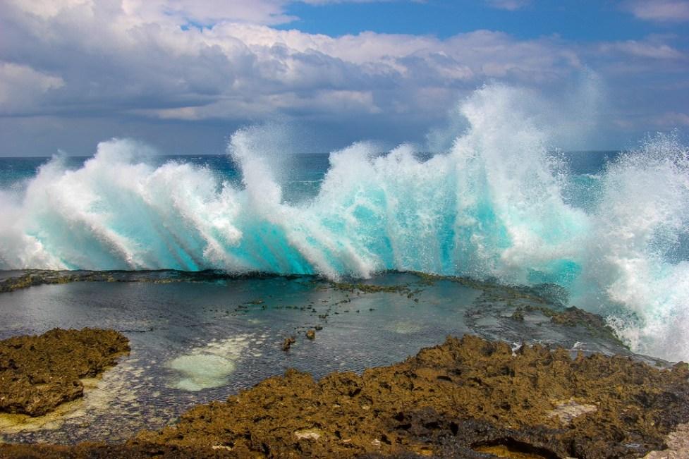 Water sprays from waves crashing on rocks near Devil's Tears on Nusa Lembongan, Bali, Indonesia