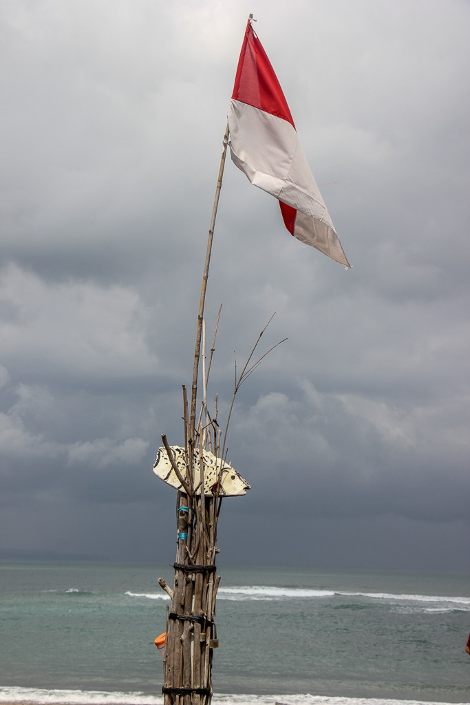 Indonesian flag flies on the beach on a stormy day in Canggu, Bali, Indonesia