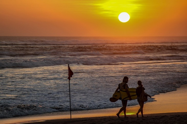 Surfers walking at sunset on Echo Beach in Canggu, Bali, Indonesia