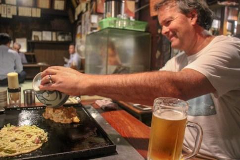 Cooking our own Okonomiyaki at Sometaro in Tokyo, Japan