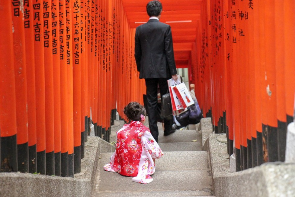 Little girl dressed in kimono on stairs under torii gates at Hie Shrine in Tokyo, Japan