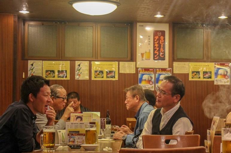 Men drinking beers at Kamiya Bar in Tokyo, Japan