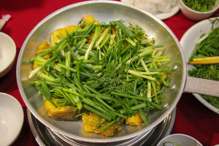 Skillet of Cha Ca with fresh herbs at Cha Ca Thang Long in Hanoi, Vietnam