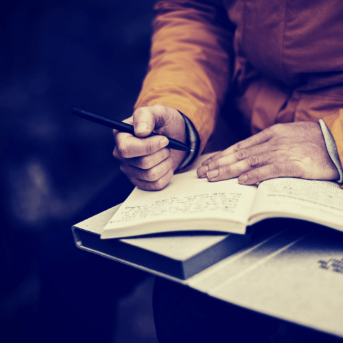 man writing in a journal - questions for self-reflection