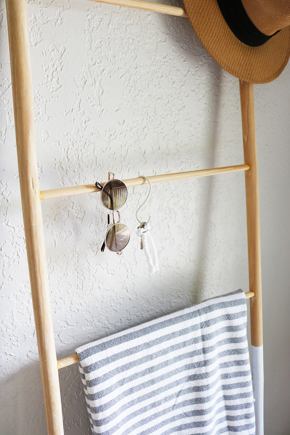 Closeup Of Dowel Ladder Leaning Against Wall With Blanket Sunglasses Key Hook And Dipped