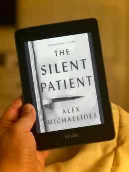 hand holding a Kindle Paperwhite, and on the screen is the book cover for The Silent Patient by Alex Michaelides