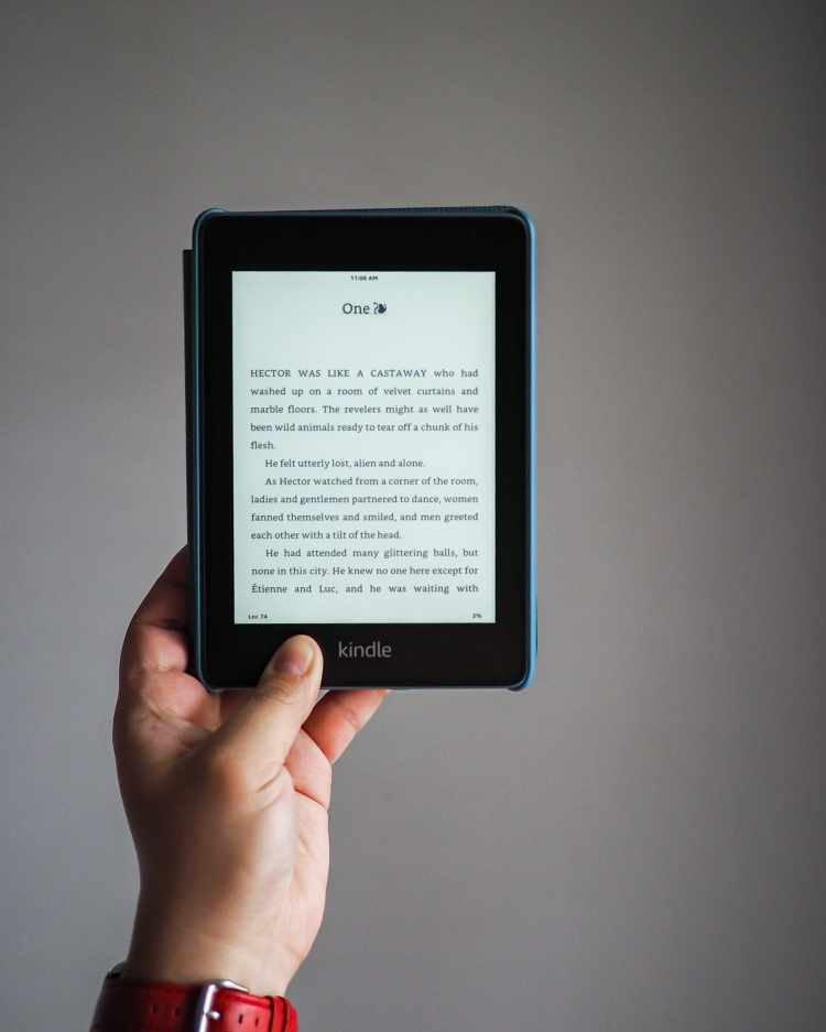 A hand holding a Kindle Paperwhite, which shows the first page of Chapter One from the book, The Beautiful Ones by Silvia Moreno-Garcia.