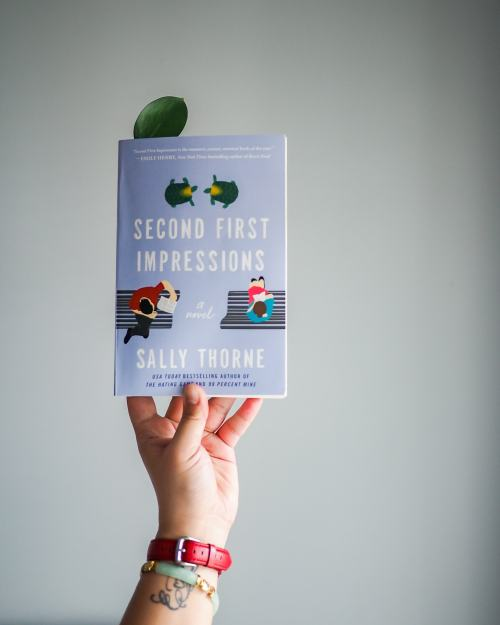 A hand holds up the book Second First Impressions by Sally Thorne. A green leaf is being used as a bookmark. The background is a gray wall.