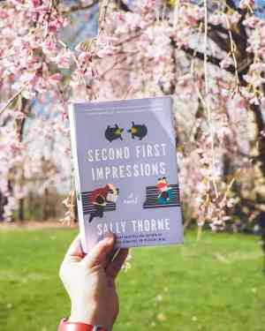 A hand holds up the book Second First Impressions by Sally Thorne. The photo is taken outdoors, and the background, there are the pink blossoms of a cherry tree.