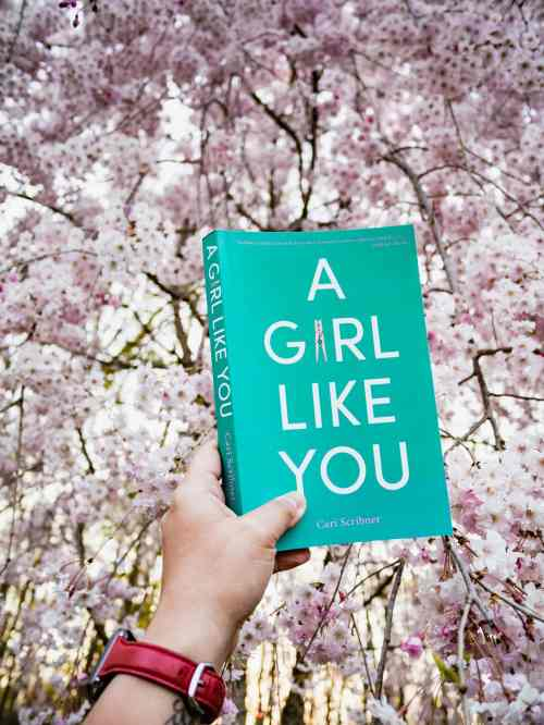 A hand holds up the book A Girl Like You in front a weeping cherry tree.
