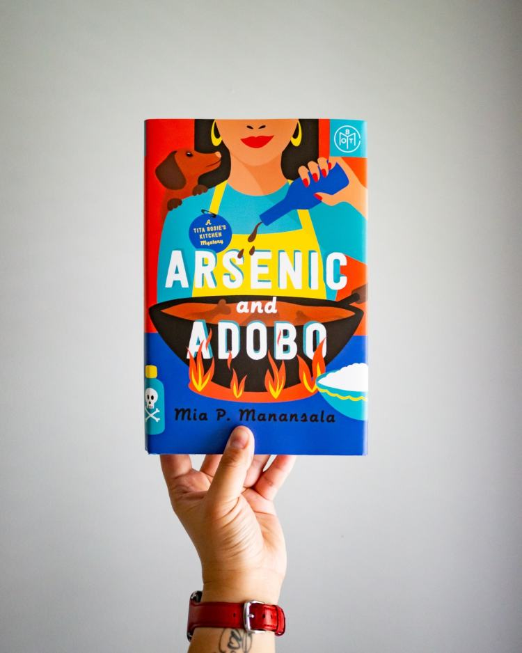 A hand is holding the book Arsenic and Adobo by Mia P. Manansala