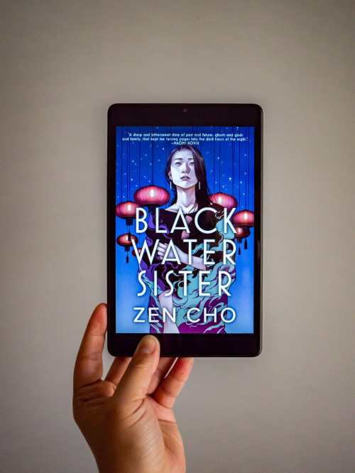 A hand is holding a tablet, which is displaying the cover for Black Water Sister by Zen Cho on its screen.