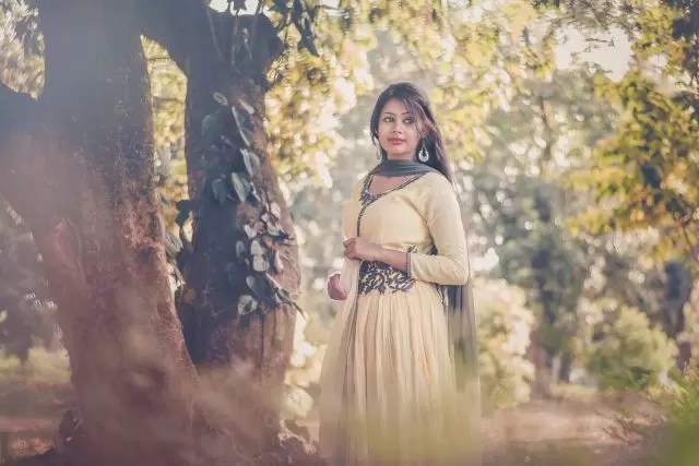 woman wearing yellow dress standing beside tree