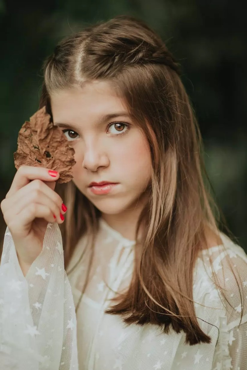 calm stylish girl with dry autumn leaf in hand looking at camera
