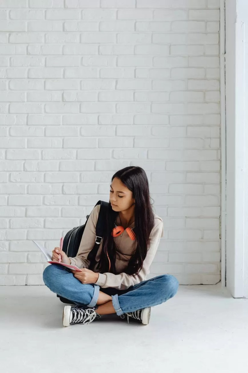 female teenager writing on her notebook while sitting on the floor