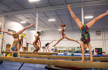 Girls workout routines on the high-beam.