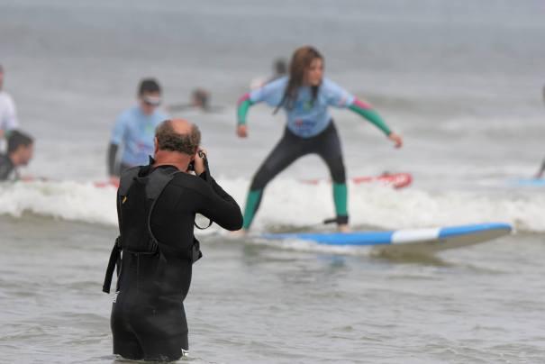 Patrick avec son appareil photo en train de prendre en photo Lou sur une vague   lors d'une journée See Surf
