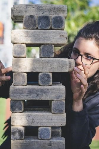 A person wearing glasses contemplates how they'll pull out the next wooden block in a game of Jenga.