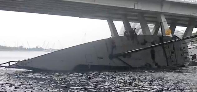 """Der Maxi """"Youuzoo"""" wird kontrolliert gekentert, damit er unter die Brücke passt."""