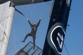 Bloß nicht fallen lassen. Trimmer Kyle Langford hängt nur an den Armen im Trampolin-Netz. © Guilain Grenier / Oracle Team USA