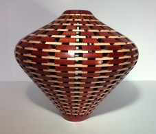 """Red & White 7.5"""" high x 7""""; diameter. Woods used are Bloodwood and Maple. There are 40 open segment rows with 18 segments each and 4 segmented rows with 12 segments."""