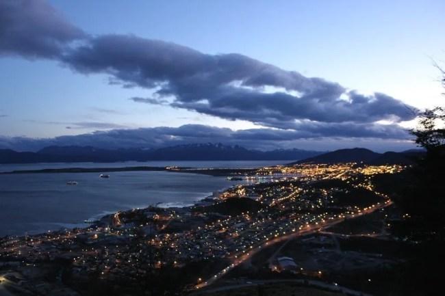 Cidade de Ushuaia vista de cima do hotel Arakur, ao anoitecer, quando as luzes das casas começam a se acender.