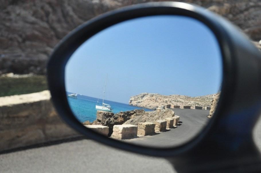 Foto de um espelho de carro. Refletido nele, um mar com um barco e uma estrada sinuosa.