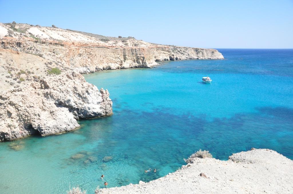 Praia de Tsigrado, em Milos, vista de cima. Mar super azul com formações rochosas claras e um barco no meio.