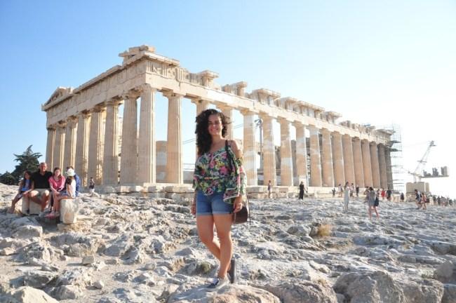 Mulher em primeiro plano, pantheon no fundo com um céu azul. Foto que ilustra o artigo quando ir para a Grécia, já que mostra vários outros turistas ao fundo.