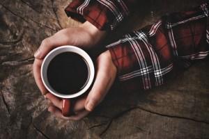 暖かい1杯のコーヒーを手にする人