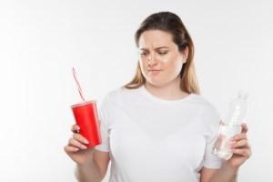 ジュースを飲みたいのを我慢する女性