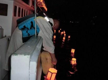 清光院住職がお経と供にひとつひとつ灯籠を海へ流しています