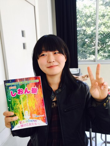Natsumi, the artist, with a copy of the handbook