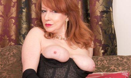 Mature babe in geile lingerie doet een striptease bij de kerstboom