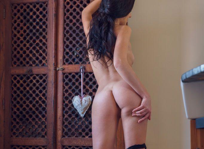 Sultana, knappe vrouw met donker haar, trekt sexy lingerie uit