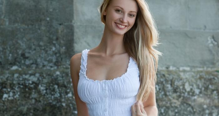 Een mooie blonde vrouw in een zomerjurkje, ze gaat ook naakt