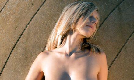 Knappe blonde vrouw doet aan naakt poseren
