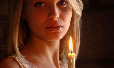 Knappe naakte vrouw met een brandende kaars