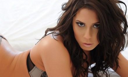 Georgie B in lingerie, op een bed met spijlen