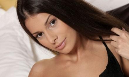 Lia Taylor, knappe brunette met grote borsten, alleen op bed