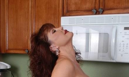 Geile oudere vrouw in de keuken en in een pornovideo