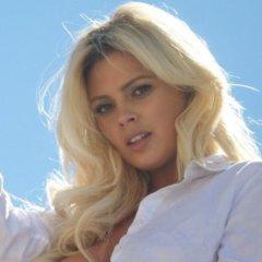 Mooie blonde vrouw heeft een strakke spijkerbroek en hoge hakken aan