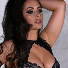 Donker haar van Anastasia Harris past goed bij haar zwarte lingerie