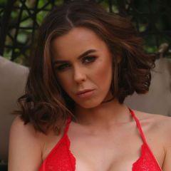 Jennifer Ann zit in de tuin, ze heeft mooie rode lingerie aan