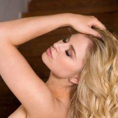 De mooie blonde Maya Rae, naakt op de houten trap