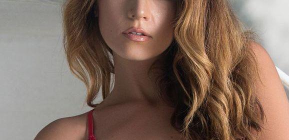 Knappe Playboy brunette trekt haar sexy roze body uit
