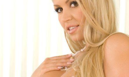 Charmane, lekker blond ding, ligt op bed opwindend te doen